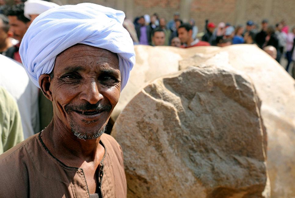 Египетский рабочий возле статуи древнеегипетского фараона Рамзеса Второго, обнаруженой археологами в районе Матария в Каире
