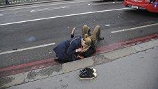 Девушка помогает раненному мужчине на Вестминстерском мосту в Лондоне