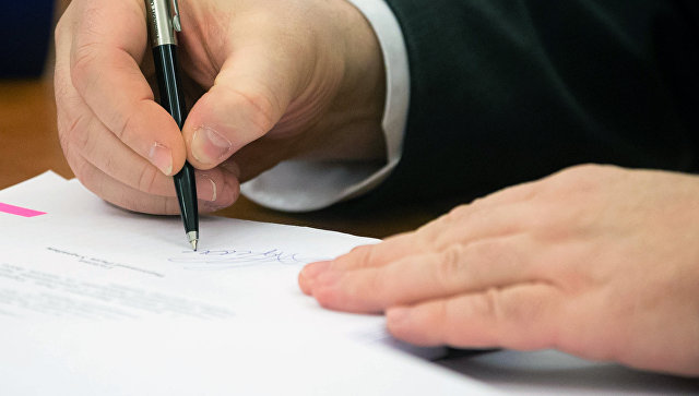 Президент Украины Петр Порошенко подписывает документ. Архивное фото