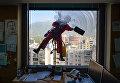 Работник моет окно офисного здания в Каракасе, Венесуэла