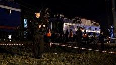Сотрудники правоохранительных органов стоят в оцеплении на месте столкновения пассажирского поезда и электрички в районе улицы Герасима Курина в Москве