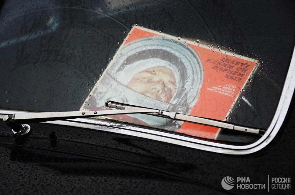 Карточка с фотографией космонавта Юрия Гагарина под лобовым стеклом ретро-автомобиля