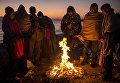 Мигранты греются у костра на греческом острове Лесбос