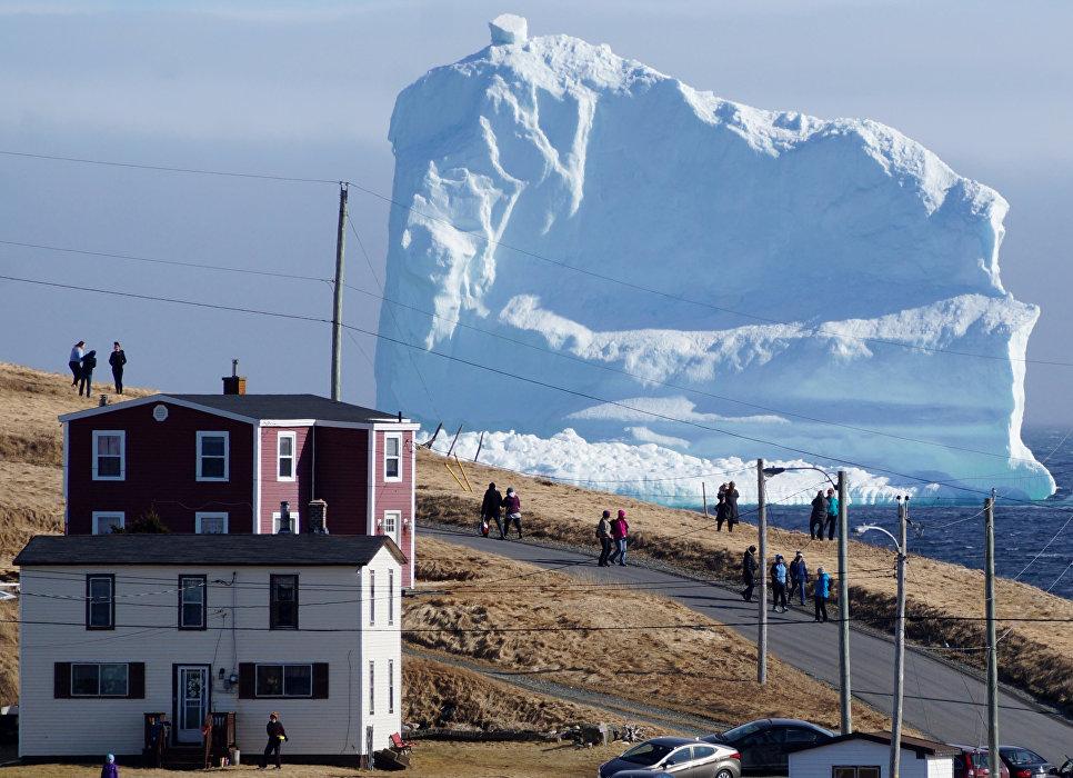 Жители Ферриленда рассматривают первый в этом сезоне айсберг, который дрейфует в месте под названием Аллея айсбергов, Канада
