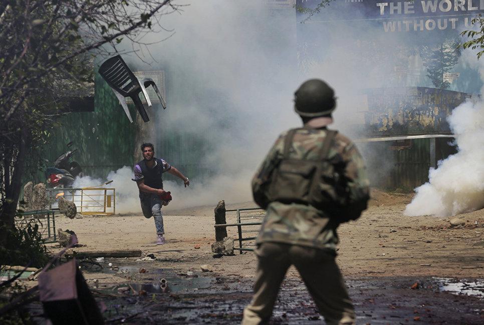 Студент кидает стул в полицейского в Кашмире, Индия