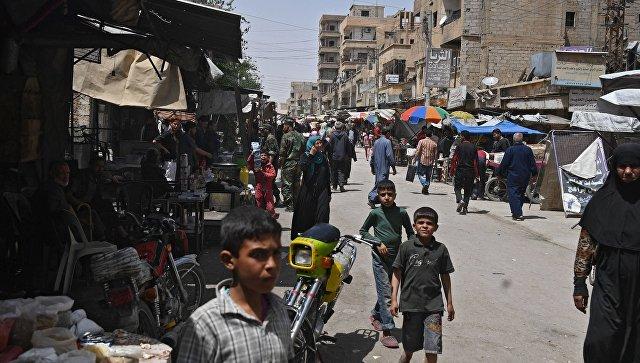 Жители на улице в сирийском городе Дейр-эз-Зор. Архивное фото