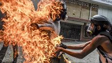 Демонстратор после взрыва бензобака полицейского мотоцикла во время столкновений в знак протеста против президента Венесуэлы Николаса Мадуро в Каракасе, 3 мая 2017