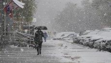 Прохожие во время снегопада на Ленинском проспекте в Москве. Архивное фото