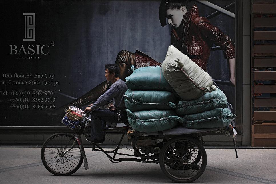 Житель Пекина на трехколесном велосипеде, нагруженном товарами, проезжает мимо Международного торгового центра Житань