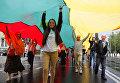 """Жители Литвы несут флаг своей страны во время празднования 25-летней годовщины """"Балтийской цепи"""""""