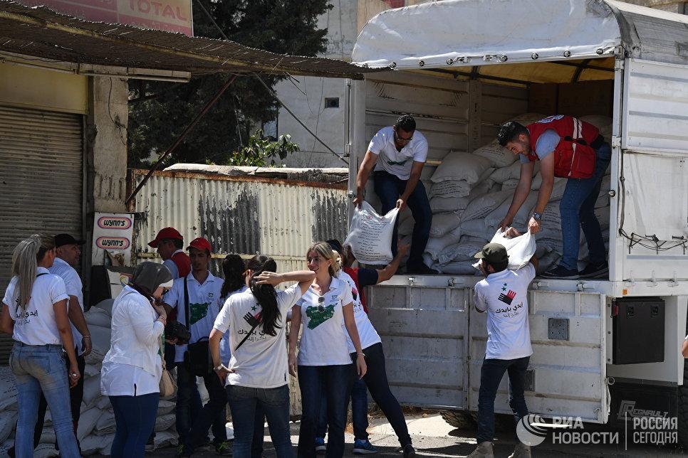 Представители Сирийского арабского красного полумесяца и Дамаскской молодежной волонтерской команды разгружают грузовик с гуманитарной помощью для жителей квартала Кабун в пригороде Дамаска