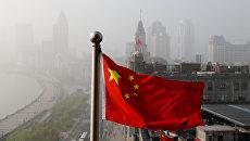 Флаг Китая развевается над офисными зданиями в Шанхае. Архивное фото