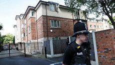 Сотрудник полиции в районе Чорлтон в Южном Манчестере, где был арестован подозреваемый в причастности к теракту. 23 мая 2017