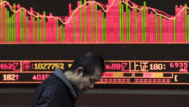 Прохожий на фоне табло с биржевыми котироваками в Шанхае, КНР. Архивное фото