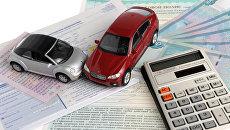 Два автомобиля, калькулятор на фоне полиса, извещения и денег. Архивное фото