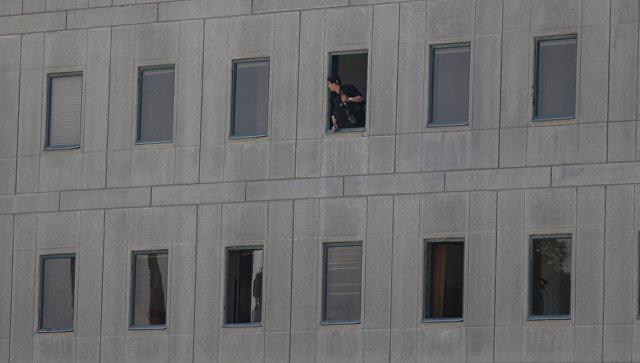 Иранский полицейский в окне здания парламента в Тегеране. 7 июня 2017