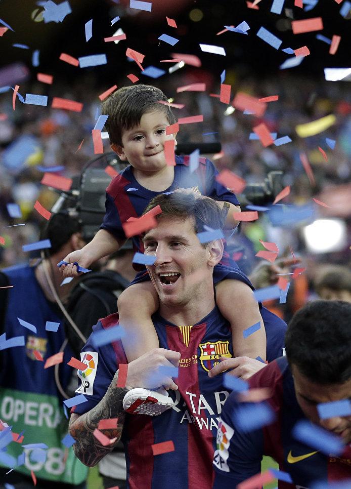 Нападающий футбольного клуба Барселона Лионель Месси с сыном радуются победе на стадионе в Барселоне