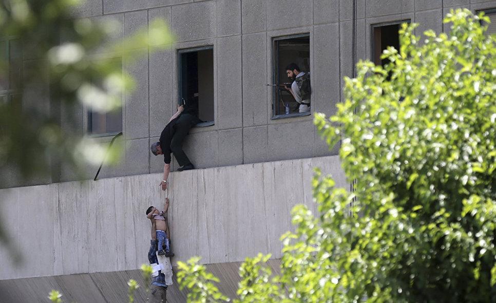 Человек передает ребенка охраннику из окна здания парламента Ирана в Тегеране. 7 июня 2017 года