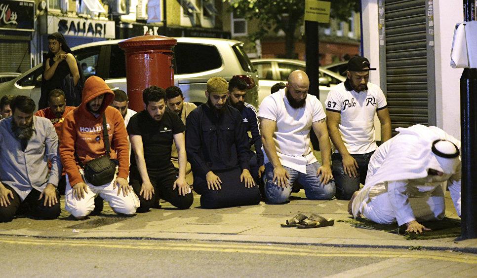 Люди молятся на месте наезда фургона на толпу людей в Лондоне. 19.06.2017