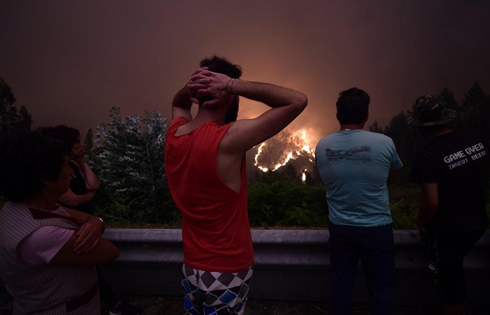 Жители деревни Мега Фандейра наблюдают за лесными пожарами
