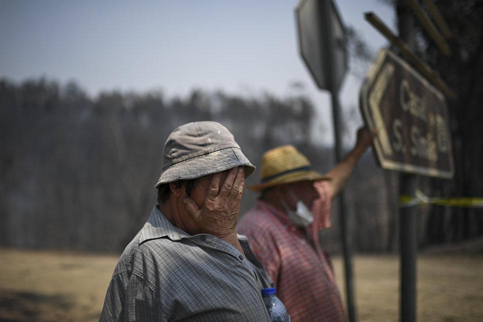 Жители наблюдают за лесными пожарами в Фигейро-дос-Виньосе, Португалия