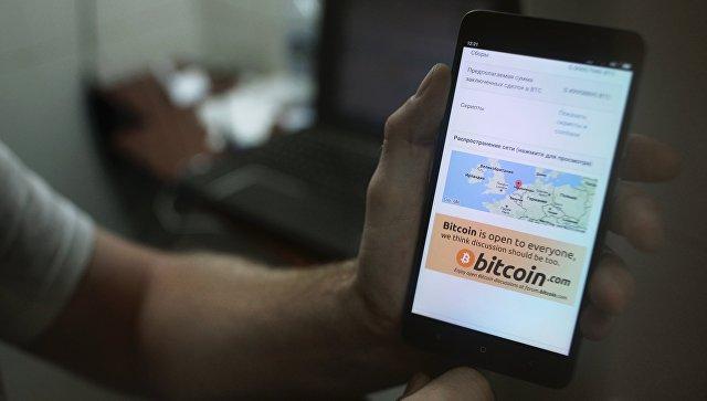 Демонстрация на смартфоне мобильного приложения для работы с криптовалютой биткоин в стационарном обменном пункте криптовалют в Москве. Архивное фото