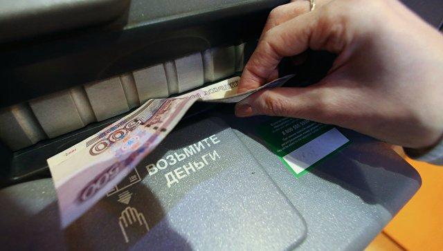 Женщина получает наличные деньги из банкомата в отделении Сбербанка РФ в Калининграде