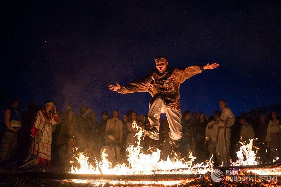 Мужчина прыгает через костер на этнофестивале Солнцестояние в Омской области