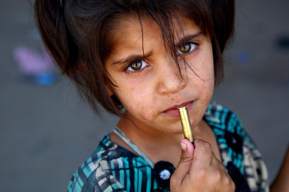 Сирийская девочка с патроном в руке в деревне Джазра в пригороде Ракки