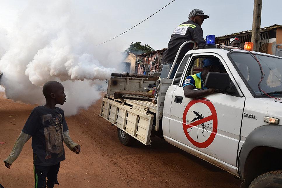 Мальчик рядом с автомобилем, распыляющим инсектициды для уничтожения комаров в Кот-д'Ивуаре