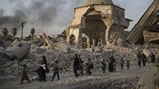 Местные жители прохят мимо разрушенной мечети в Мосуле, Ирак