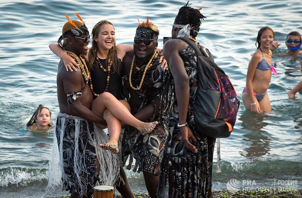 Девушка фотографируются с иностранцами на пляже в Судаке