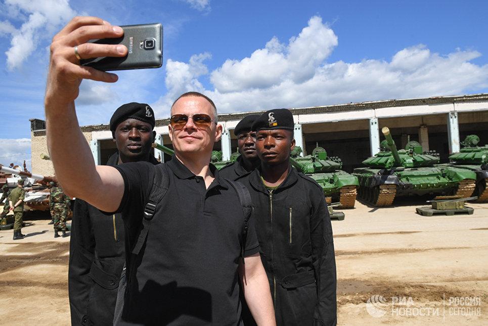 Посетитель фотографируется с участниками команды Зимбабве перед началом репетиции международного этапа конкурса Танковый биатлон Армейских международных игр -2017 в Алабино