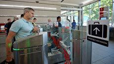 Пассажиры проходит через турникеты на одной из станций метро в Москве. Архивное фото