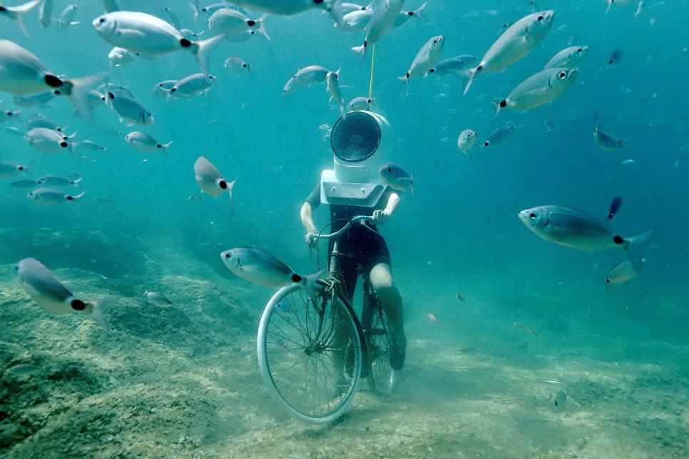 Женщина на велосипеде в подводном парке Пулы, Хорватия. 1 августа 2017