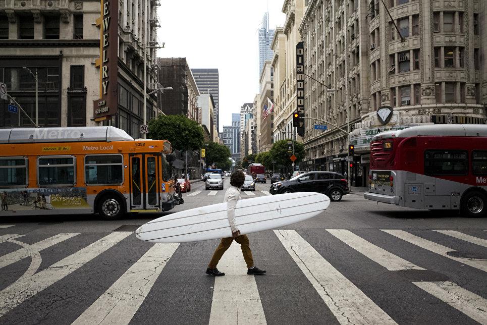 Мужчина переходит дорогу в центре Лос-Анджелеса
