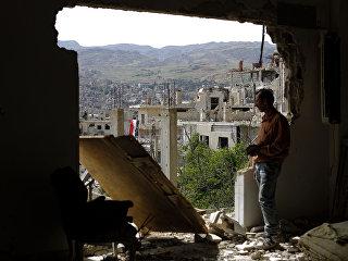 Мужчина смотрит на руины в окрестностях Дамаска после  авиаударов коалиции во главе с США по позициям ИГИЛ. Архивное фото