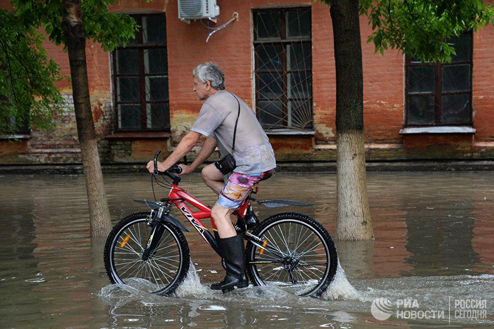 Мужчина на затопленной улице Уссурийска. 7 августа 2017