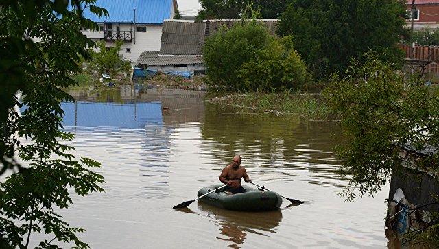 Мужчина на лодке во время наводнения в Уссурийске. Архивное фото