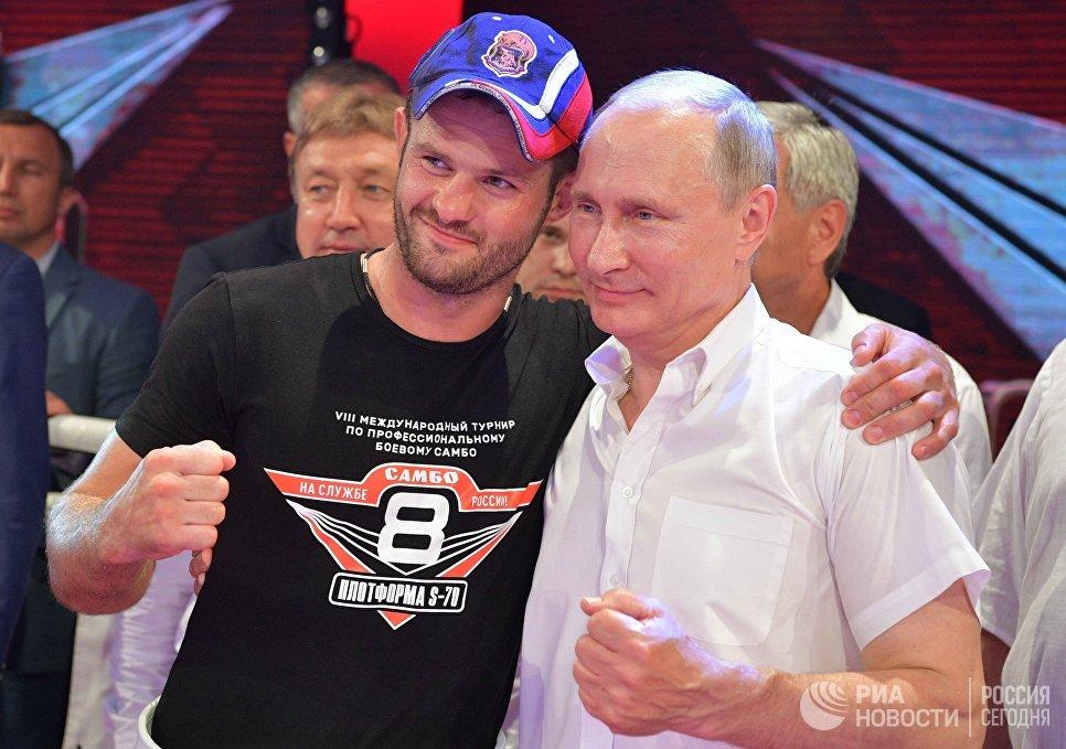 Владимир Путин фотографируется с чемпионом мира и Европы по универсальному бою, чемпионом России по рукопашному бою Дмитрием Бикревым на Международном турнире по профессиональному боевому самбо Плотформа S-70
