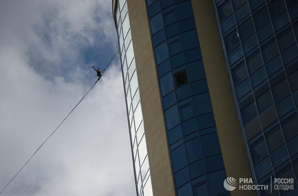 Канатоходец Максим Кагин идет по стропе, натянутой на высоте 126 метров между двумя небоскребами жилого комплекса Чемпион Парк, в Екатеринбурге