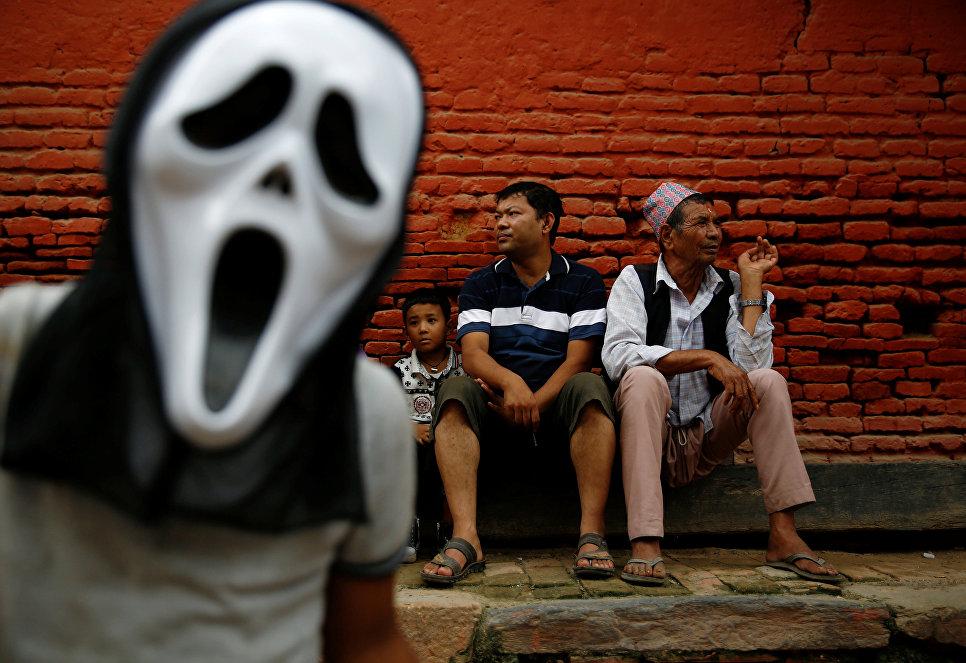 Люди наблюдают за парадом в честь фестиваля Неку-Джатра-Матайя, или фестиваля огней, в Лалитпуре, Непал