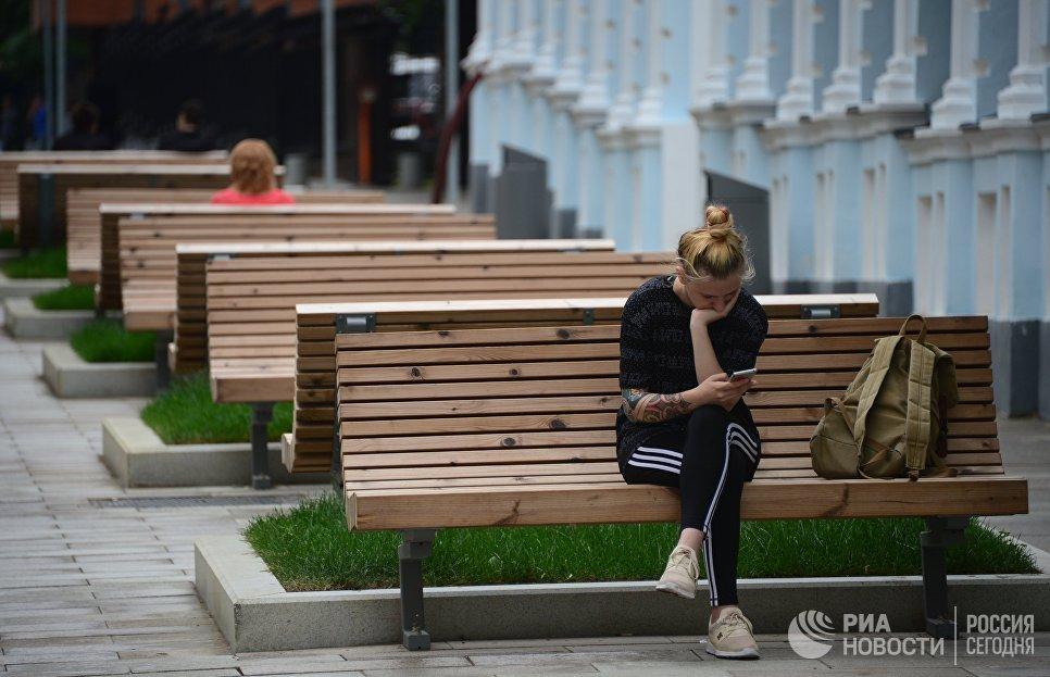 Девушка сидит на скамейке в 3-м Голутвинском переулке в Москве