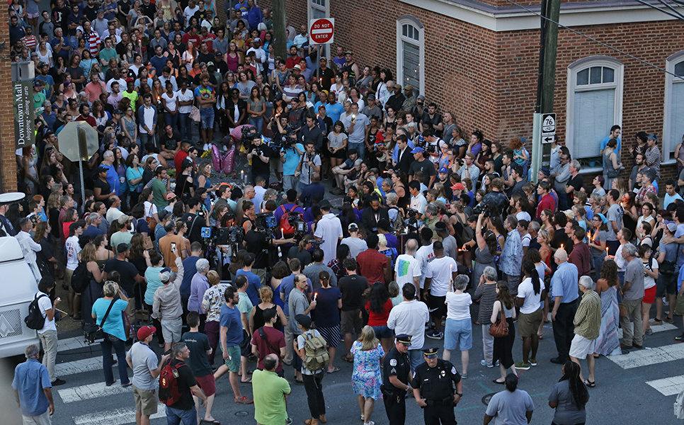 Скорбящие собрались на месте наезда автомобиля на участников протеста в Шарлоттсвилле, штат Вирджиния. 13 августа 2017