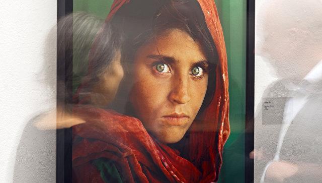 Портрет афганской девушки по имени Шарбат Гула на выставке работ фотографа Стива МакКарри