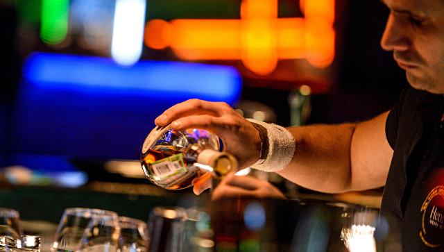 Бармен разливает напитки за барной стойкой в  клубе. Архивное фото