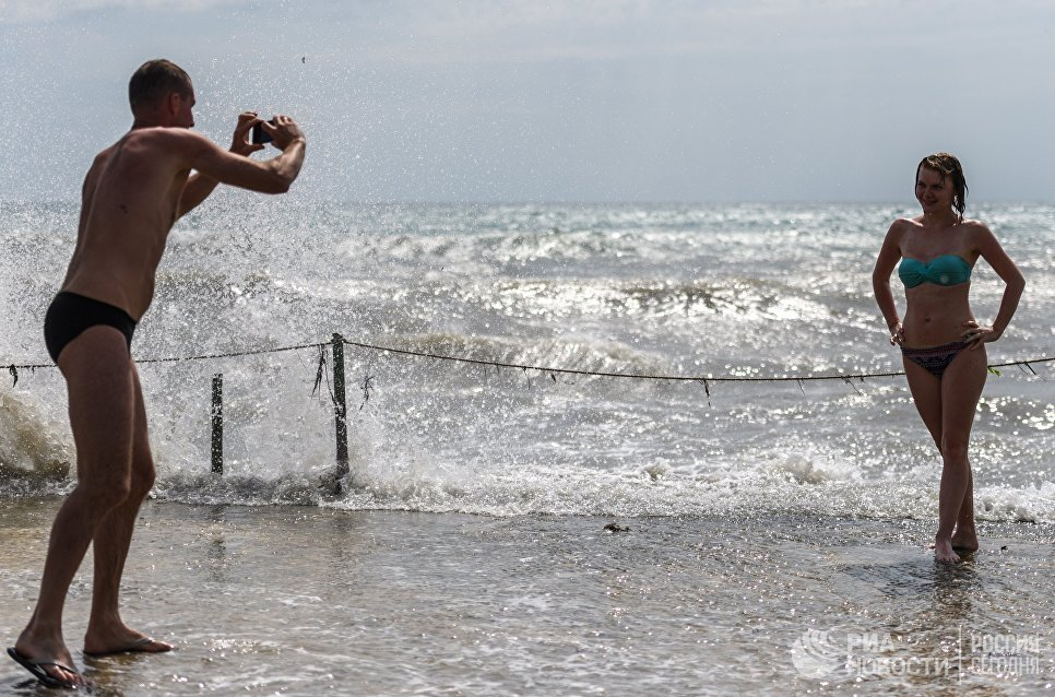 Отдыхающие фотографируются на пляже в Коктебеле