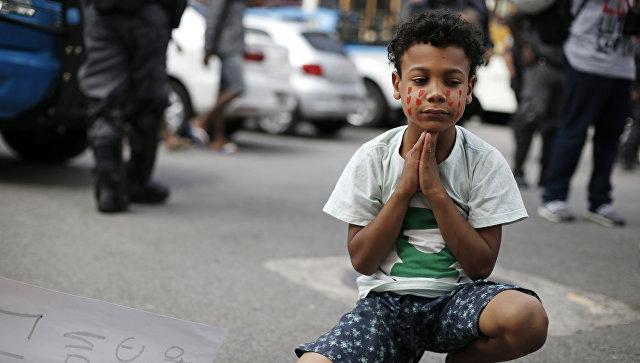 Мальчик во время акции протеста против полицейских в Рио-де-Жанейро, Бразилия. 22 августа, 2015