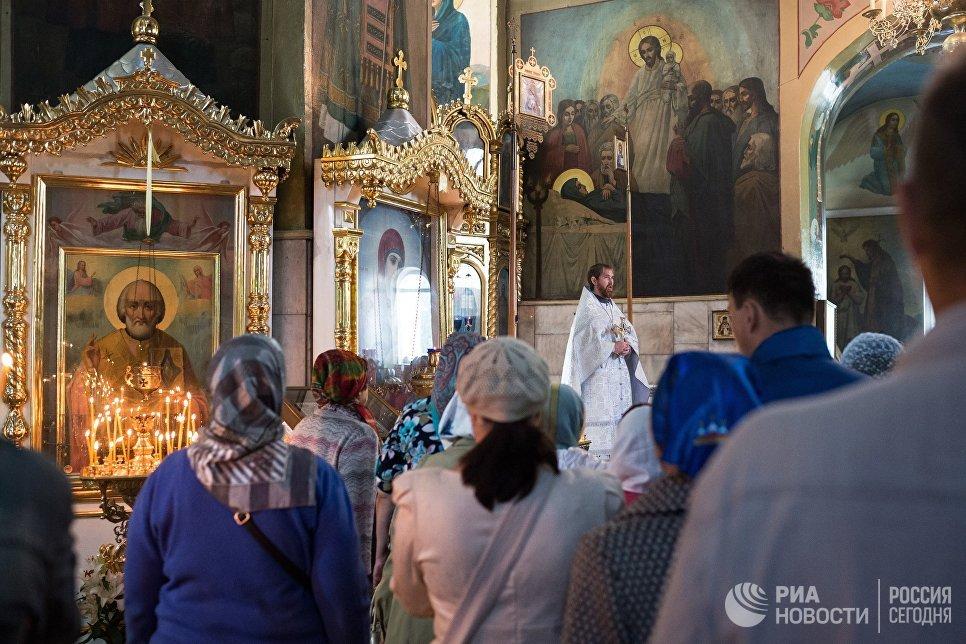 Священнослужитель и верующие во время богослужения в честь праздника Преображения Господня в соборе Воздвижения Креста Господня в Омске. 19 августа 2017