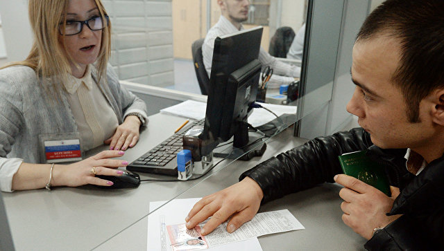 Иностранный гражданин разговаривает с сотрудником Единого миграционного центра Московской области. Архивное фото